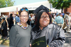 Scholarship student right during graduation ceremony, standing with Educational Services Manager, Lori Arteaga