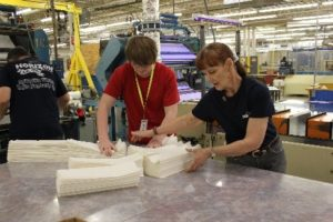 student working alongside plant employee breaking paper in manufacturing facility