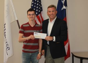 student receiving scholarship check from Vice President of Operations